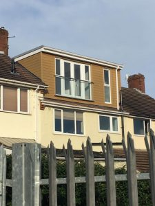 A tan color flat roof dormer loft conversion in Bristol with a juliet balcony