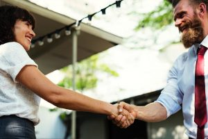 A man and woman shaking hands after discussing a loft conversion project