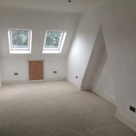 A Velux loft conversion with white walls and beige carpet in Bristol